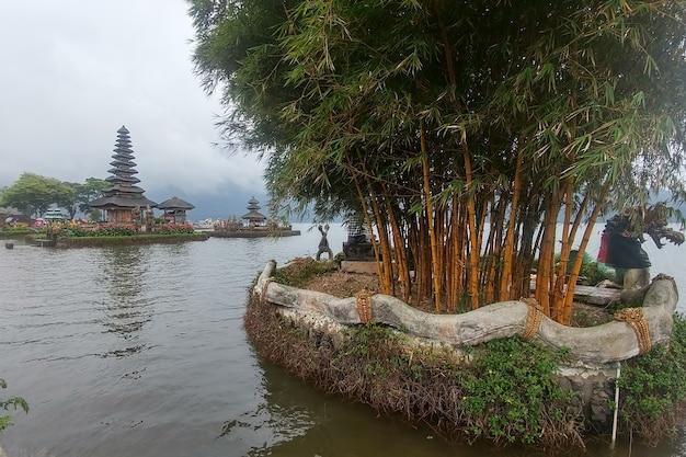 Bamboo trees and ulun danu temple on background beratan lake in bali indonesia