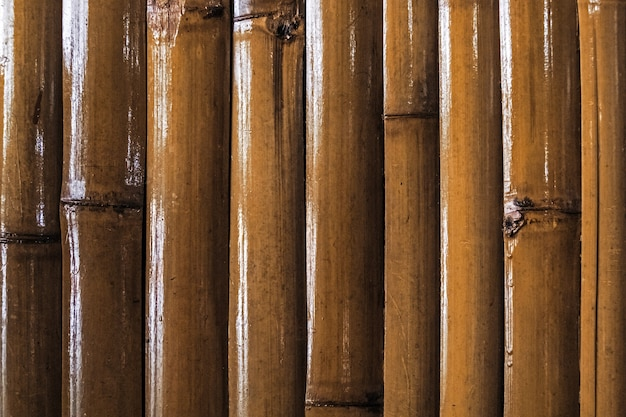 竹の壁または竹の柵のテクスチャの背景。閉じる。竹の壁は黄色のニスを塗った茎です。