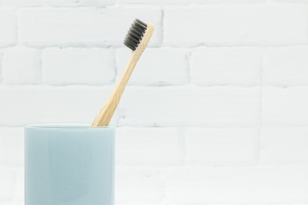 Bamboo wooden toothbrushes with black bristles in blue glass against white brick wall background. ecofriendly lifestyle, concept zero waste.