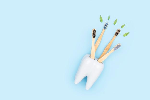 Бамбуковые деревянные зубные щетки с зелеными листьями в белом держателе зубной щетки в форме зуба. зубоврачебная медицинская помощь концепция плоской планировки. копировать пространство экологичные товары