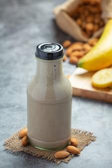 Frullato di banana e mandorle in bottiglia su sfondo scuro