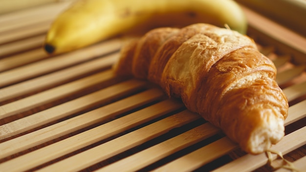 素朴な木製の背景にバナナとクロワッサン。セレクティブフォーカス、水平。