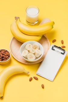 Банан и молоко на желтом бумажном фоне с пустым буфером обмена для текста