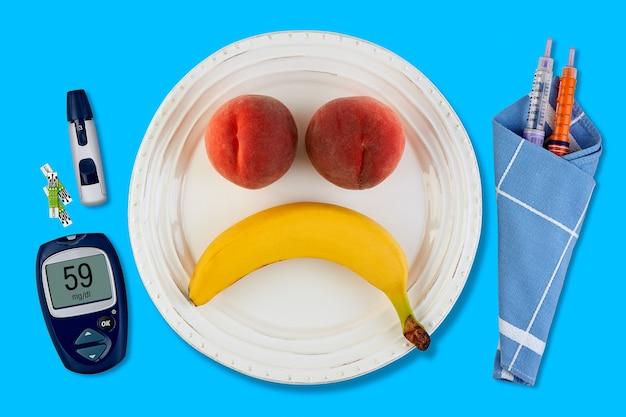 Банан и персик в виде грустного смайлика на белой тарелке и ручка для инсулиновых шприцев