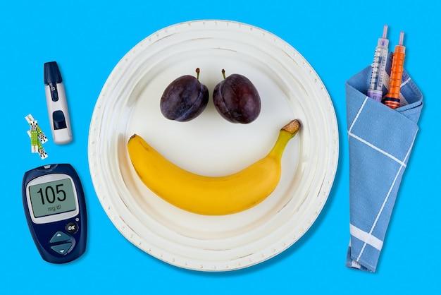 Банан и слива в виде улыбающегося смайлика на белой тарелке и ручка для инсулиновых шприцев
