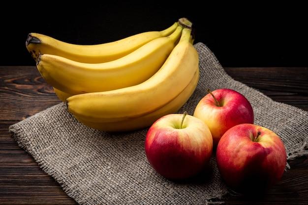 Банан и красные яблоки на темном деревянном фоне.