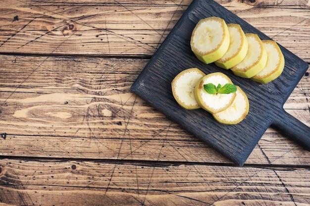 木製の素朴な背景にミントとバナナとスライスしたバナナの断片。上面図、コピースペース