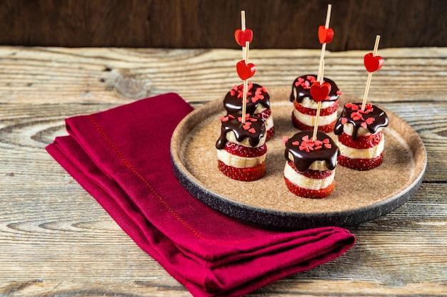 발렌타인 데이를위한 오리지널 애피타이저 인 접시에 초콜릿 글레이즈를 넣은 바나나와 딸기 카나페. 고품질 사진