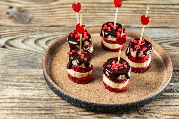 바나나와 딸기 카나페를 접시에 담은 초콜릿 글레이즈, 발렌타인 데이를위한 오리지널 달콤한 애피타이저. 고품질 사진