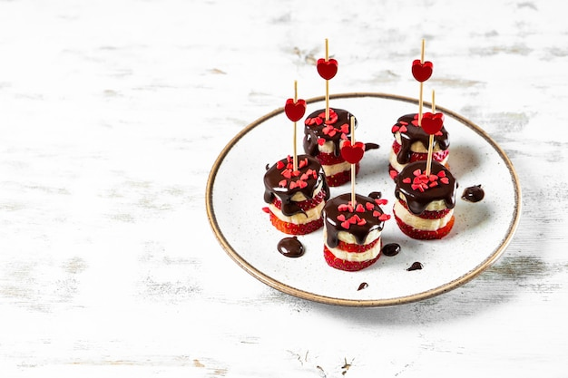 하얀 접시에 초콜렛 유약에 바나나와 딸기 카나페, 발렌타인 데이에 대한 원래 전채, 텍스트를위한 여유 공간. 고품질 사진
