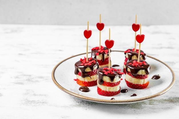흰색 접시에 초콜릿 글레이즈에 바나나와 딸기 카나페, 발렌타인 데이를위한 원래 전채. 고품질 사진
