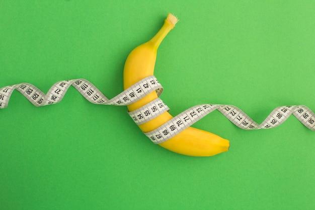 Банан и белый сантиметр на зеленом фоне