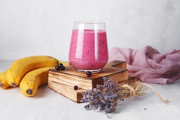 나무 서빙 보드에 유리에 바나나 베리 스무디. 신선하고 건강한 아침 식사