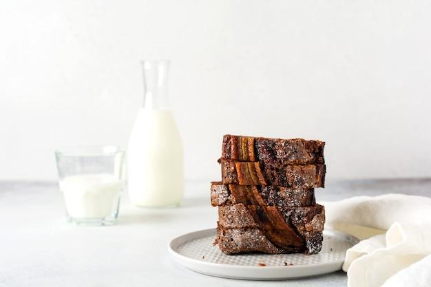 バナナブレッドは、無地の灰色のコンクリートの背景にミルクのガラスとスタックのスライスにカットされます。セレクティブフォーカス