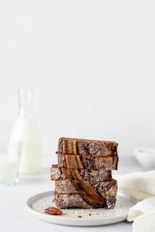 바나나 빵은 일반 회색 콘크리트 배경에 우유 한잔과 함께 스택의 조각으로 잘라냅니다.