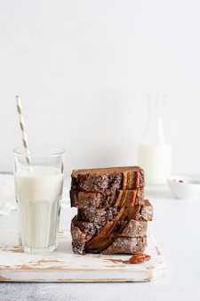 Banana bread cut into slices in stack with glass of milk on plain gray concrete table. selective focus.