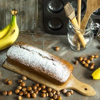 Banana bread is lying on the board among kitchen utensils, bananas and hazelnuts