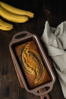 Banana bread top view on dark rustic wooden table