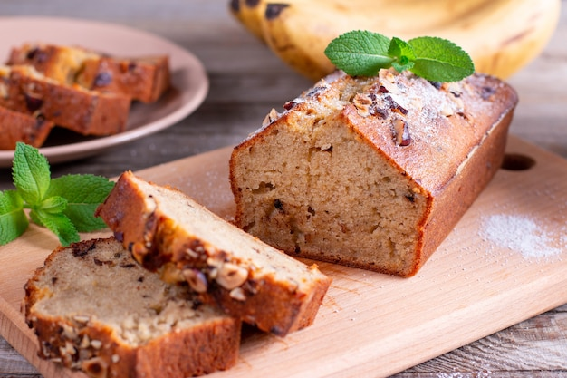 Banana bread with bananas sliced on a wooden cutting board with bananas in background