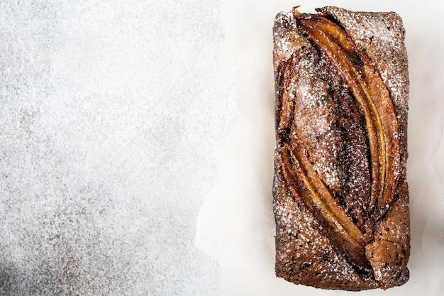 Банановый хлеб с хрустящей корочкой из корицы и сахарной пудрой на легкой бетонной поверхности. выборочный фокус, место для текста.