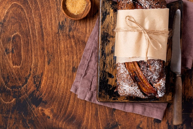 Banana bread with cinnamon crunch and sprinkled with icing sugar on light concrete background , space for text