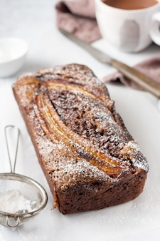 Banana bread with cinnamon crunch and sprinkled with icing sugar on light concrete table. selective focus, space for text