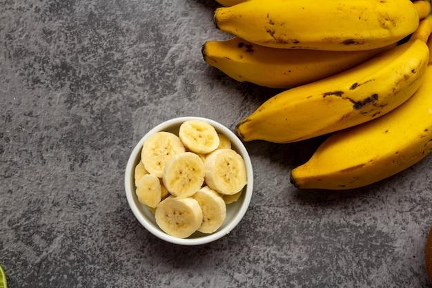 Banana bunch and sliced bananas on burnt cement surface