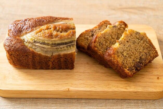 Банановый торт, нарезанный на деревянной доске