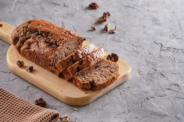Банановый торт с орехами и шоколадом на деревянной доске на сером фоне