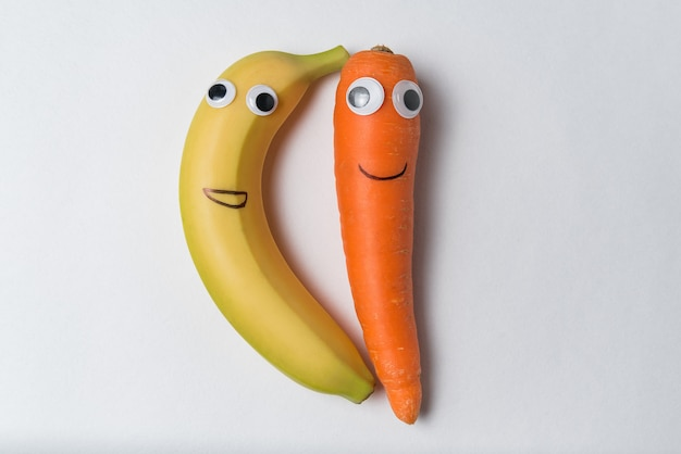 Banana and carrot with the googly eyes and smiles on white background.