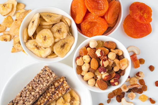 Банановые чипсы, курага, различные орехи и батончик мюсли в белых тарелках на светлой стене. вид сверху, крупный план. полезные сладкие закуски.