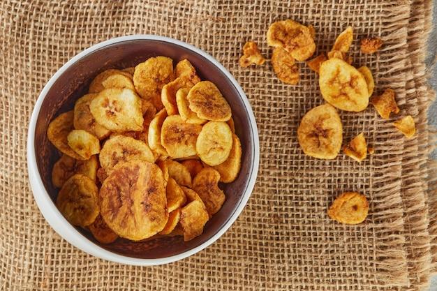 Банановые чипсы здоровая пища, сухие фрукты и полезные овощные чипсы, здоровые веганские закуски из мешковины. плоская планировка