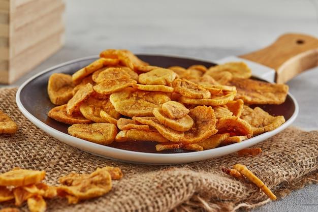 Банановые чипсы здоровая пища, сухие фрукты и полезные овощные чипсы, здоровые веганские закуски из мешковины в тарелке. закрыть вверх