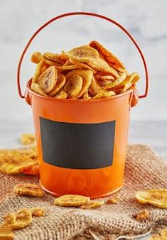 Банановые чипсы здоровая пища, сухие фрукты и полезные овощные чипсы, здоровые веганские закуски в ведре-макете и мешковина.