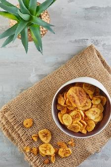 Банановые чипсы здоровая пища, сухие фрукты и полезные овощные чипсы, здоровые веганские закуски на мешковине и цветке алоэ. плоская планировка
