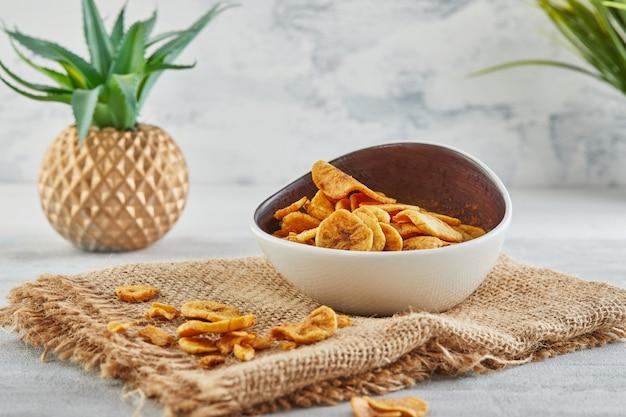 Банановые чипсы здоровая пища, сухие фрукты и полезные овощные чипсы, здоровые веганские закуски на мешковине и цветке алоэ.
