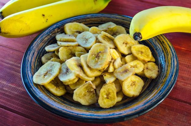 Банановые чипсы в миске и свежие бананы