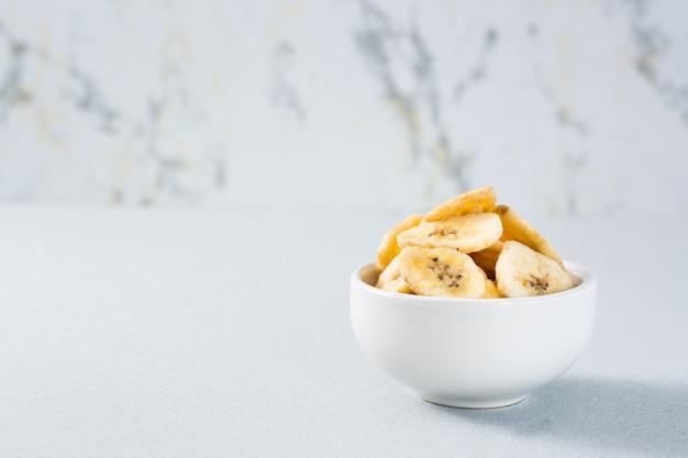 Банановые чипсы в миске на столе. быстрое питание. копировать пространство