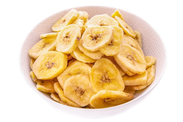 Банановые чипсы в белой тарелке на белом фоне, изолированные продукты