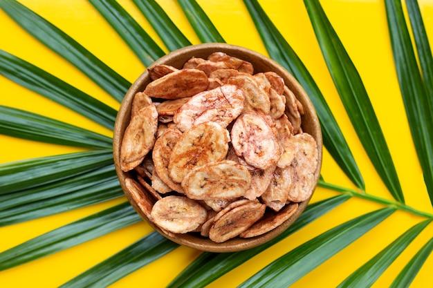 Банановые чипсы на зеленом листе с желтой поверхностью