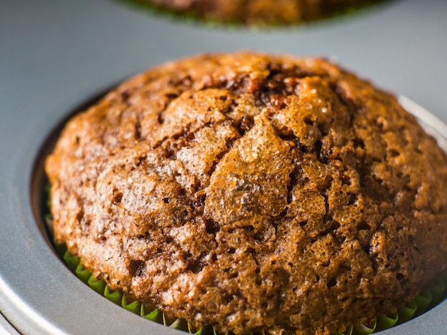 Banana chocolate muffins with caramel sugar topping on dark background