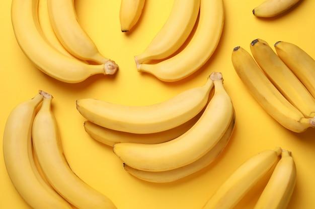 Банановые кластеры на желтом столе. свежие фрукты