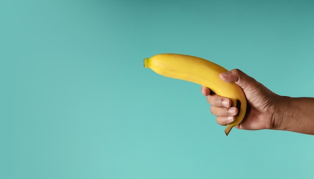 Banana concept image. hand holding a banana against the blue background, look like a gun
