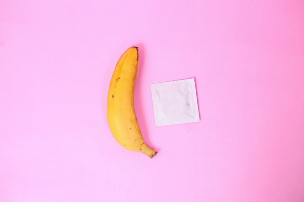 Banana and contraception isolated on pink background