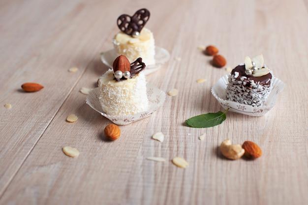 코코넛 플레이크, 진주 구슬 및 견과류가 들어간 흰색 및 어두운 초콜릿으로 덮인 바나나
