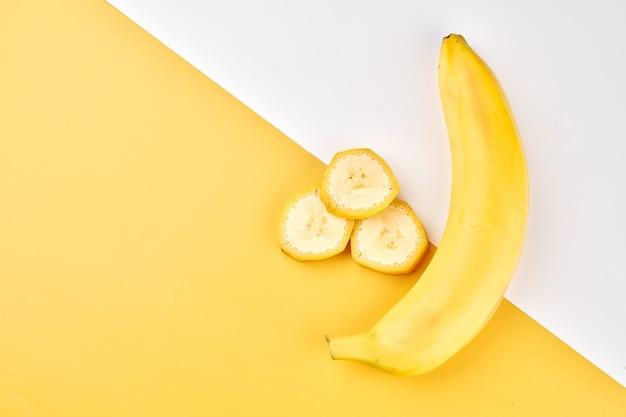 バナナの創造的な背景。全体、皮をむいた、スライスしたバナナと黄色と白の背景