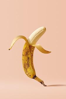 Банановый креативный плакат с темными точками. открыл летающий перезрелый плод банана на розовом фоне. разумное употребление пищи