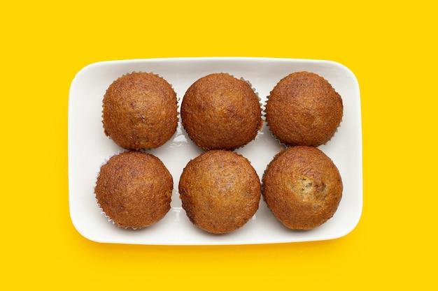 黄色の背景に白いプレートのバナナカップケーキ。