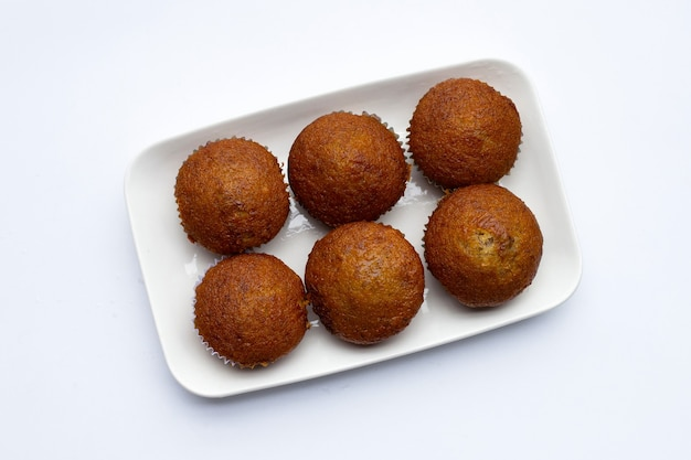 Banana cupcakes in white plate on white background.