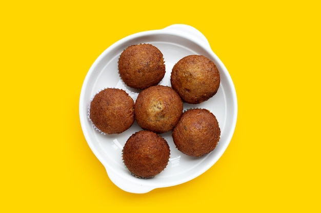 Banana cupcakes in white plate on yellow background.